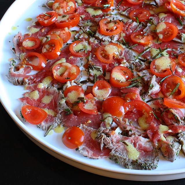 A carpaccio of raw fillet steak with tomato and rosemary